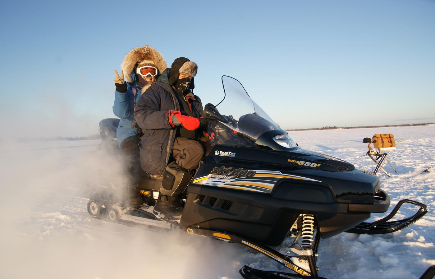 2 people enjoy a ride on a snowmobile in the Northwest territories
