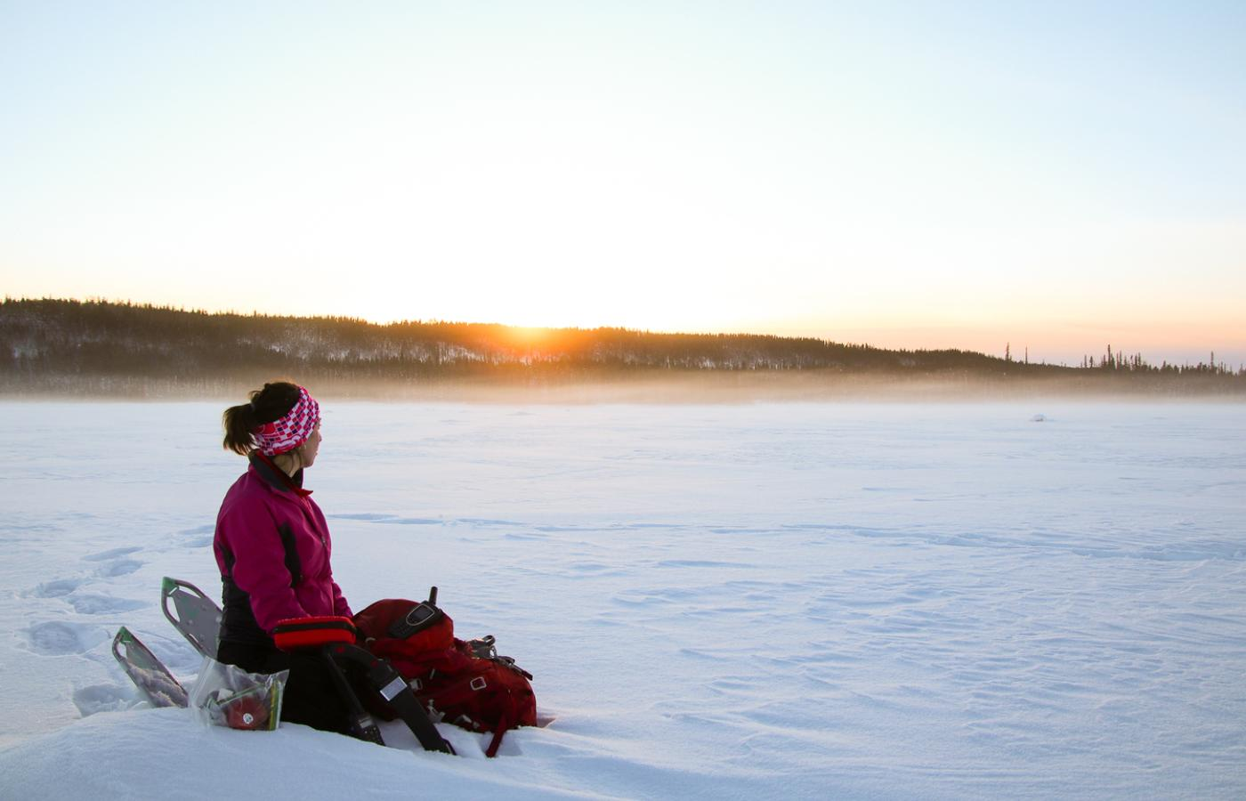 A person sits on frozen Grosbeak lake while the sun sets in Wood Buffalo National Park in the NWT