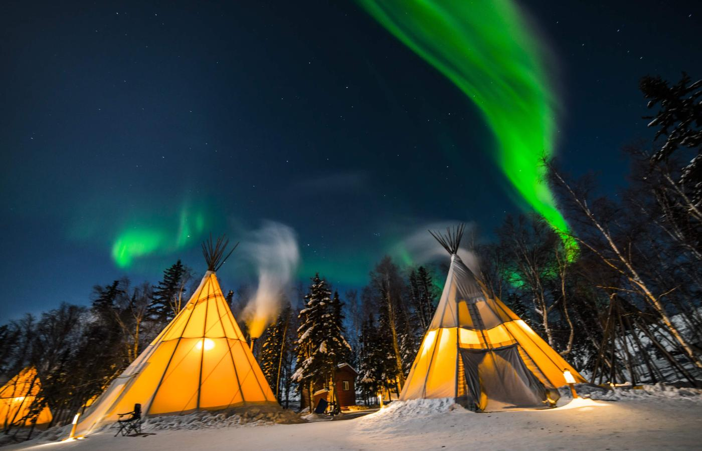 Teepee under green and blue Aurora in the night sky at Aurora Village in the Northwest Territories