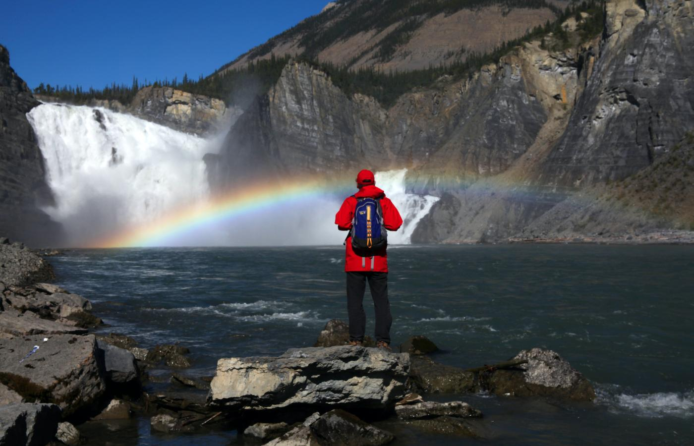 A person stand in front of Virgina falls as a rainbow beams across the water in Nahanni National Park Reserve in the Northwest territories