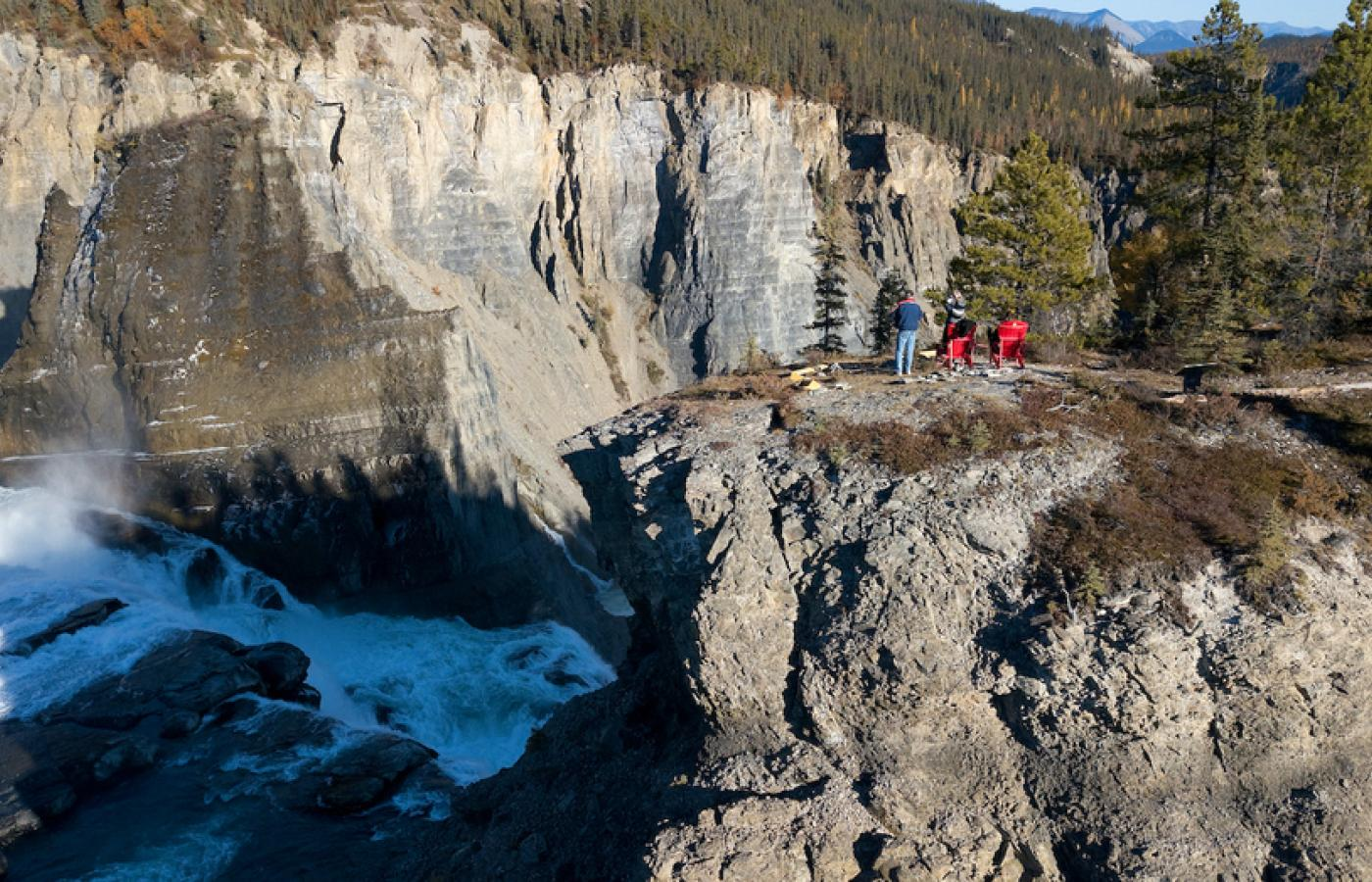 People sit a the top of a cliff viewing the breathtaking virginia falls at Nahanni National Park  in the spectacular Northwest territories