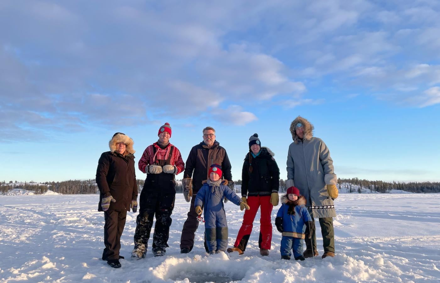 A group of people stand around a fishing hole while ice fishing the the Northwest territories