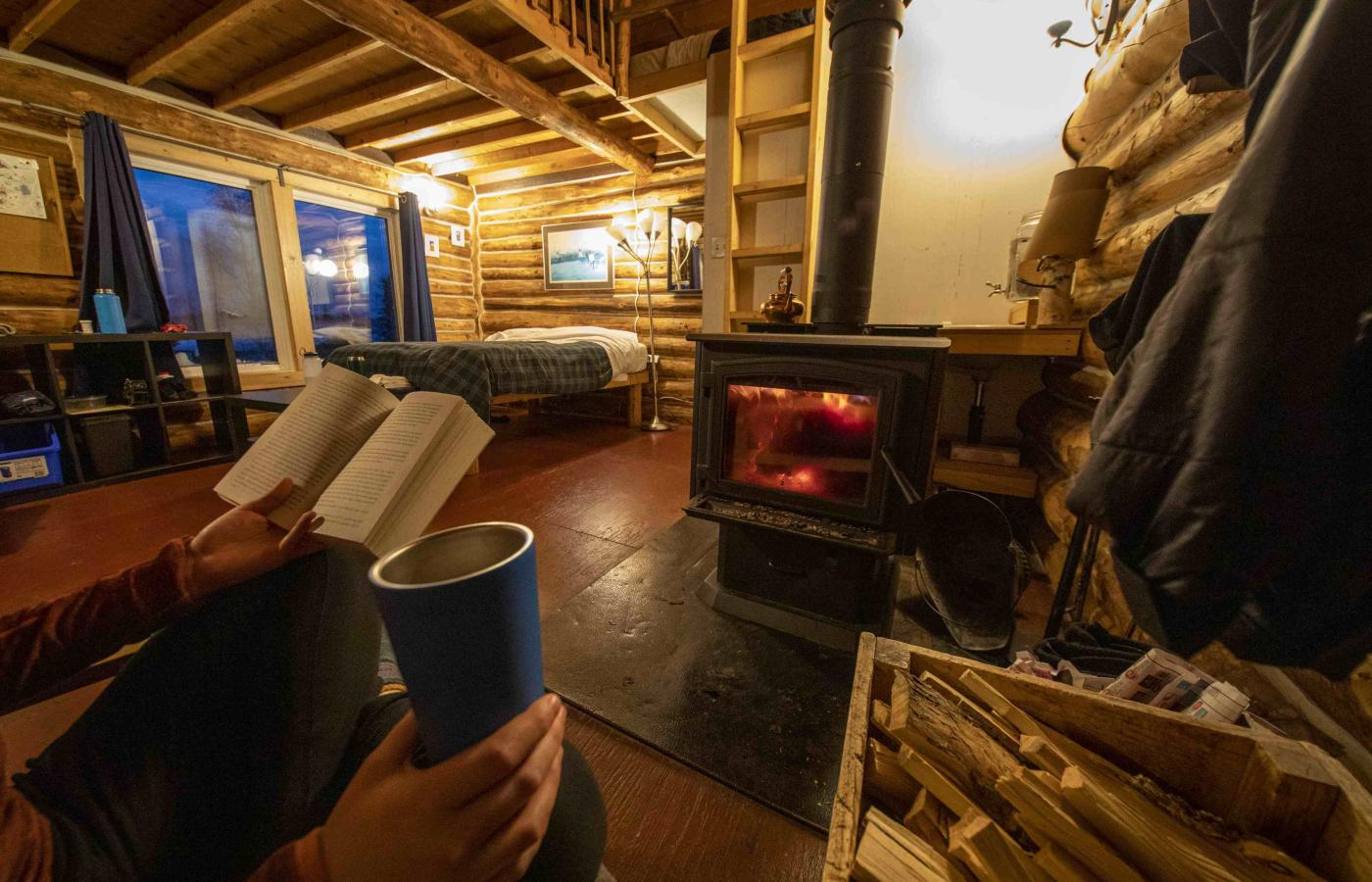 A person reads by a woodstove fire at beautiful Blachford Lake Lodge in the Northwest Territories