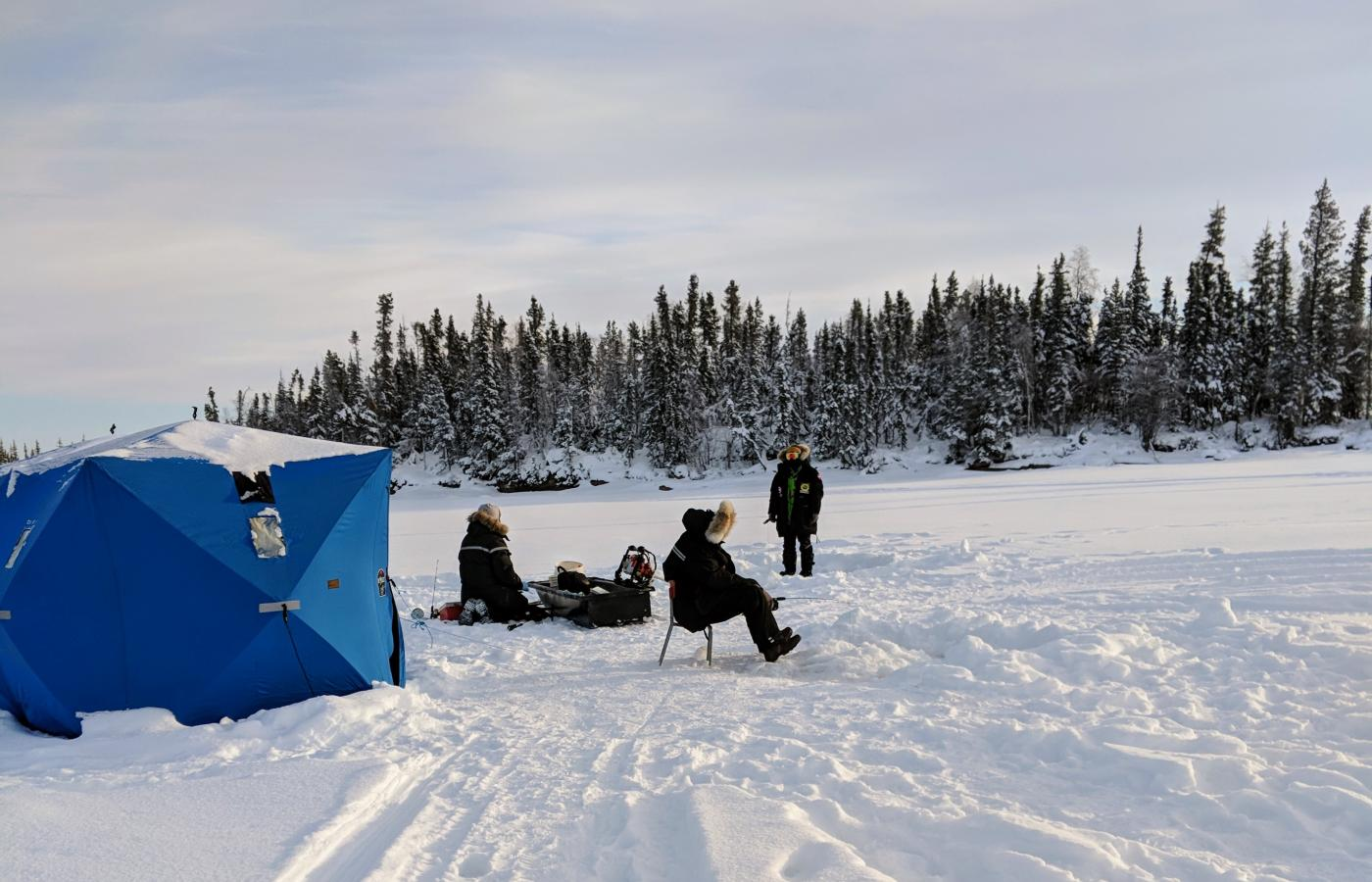 a group of travellers try to ice fish on Blachford Lake NWT