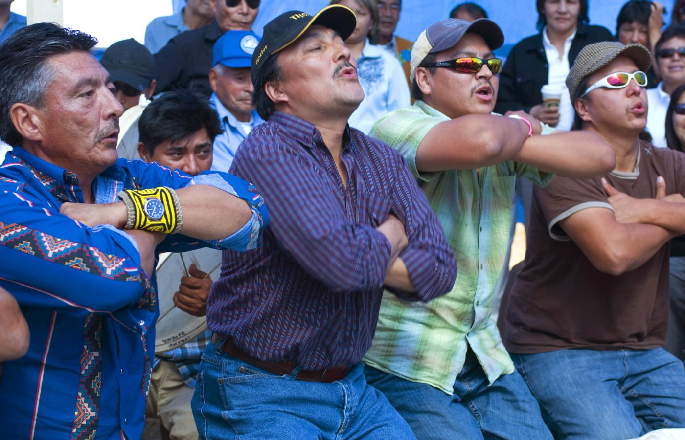 Dene dancing in a crowd with their arms crossed