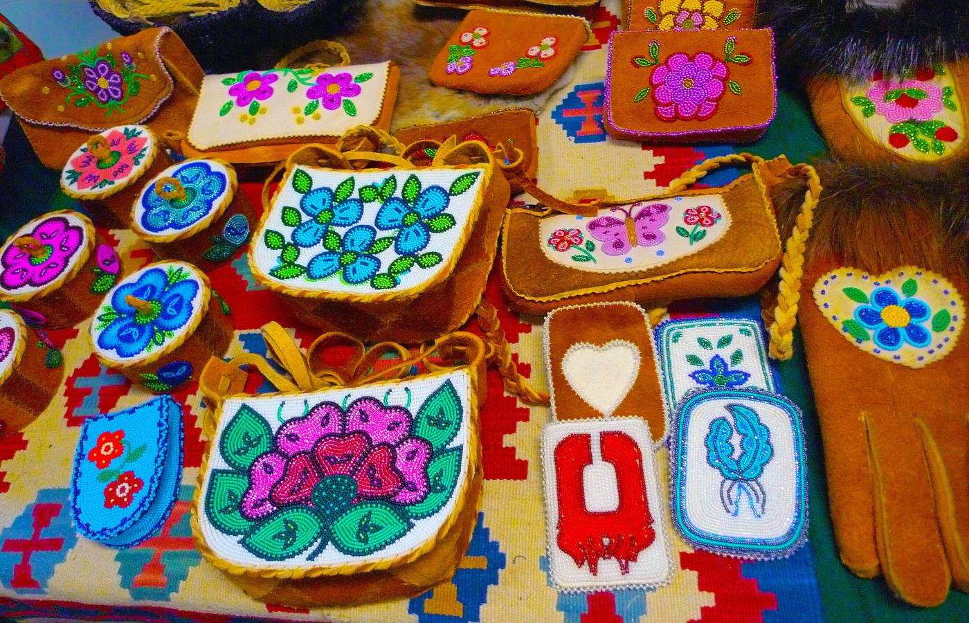 Beaded arts and crafts displayed on a table at a craft show