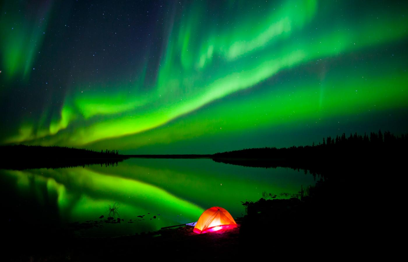 The Aurora Borealis fills the sky and is reflected in a lake in the NWT