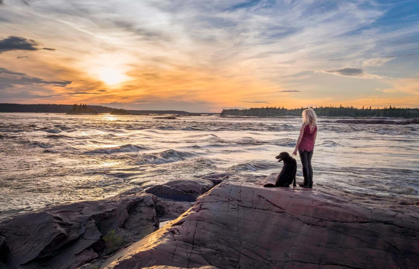 Woman and dog standing by the rapids on the Slave River