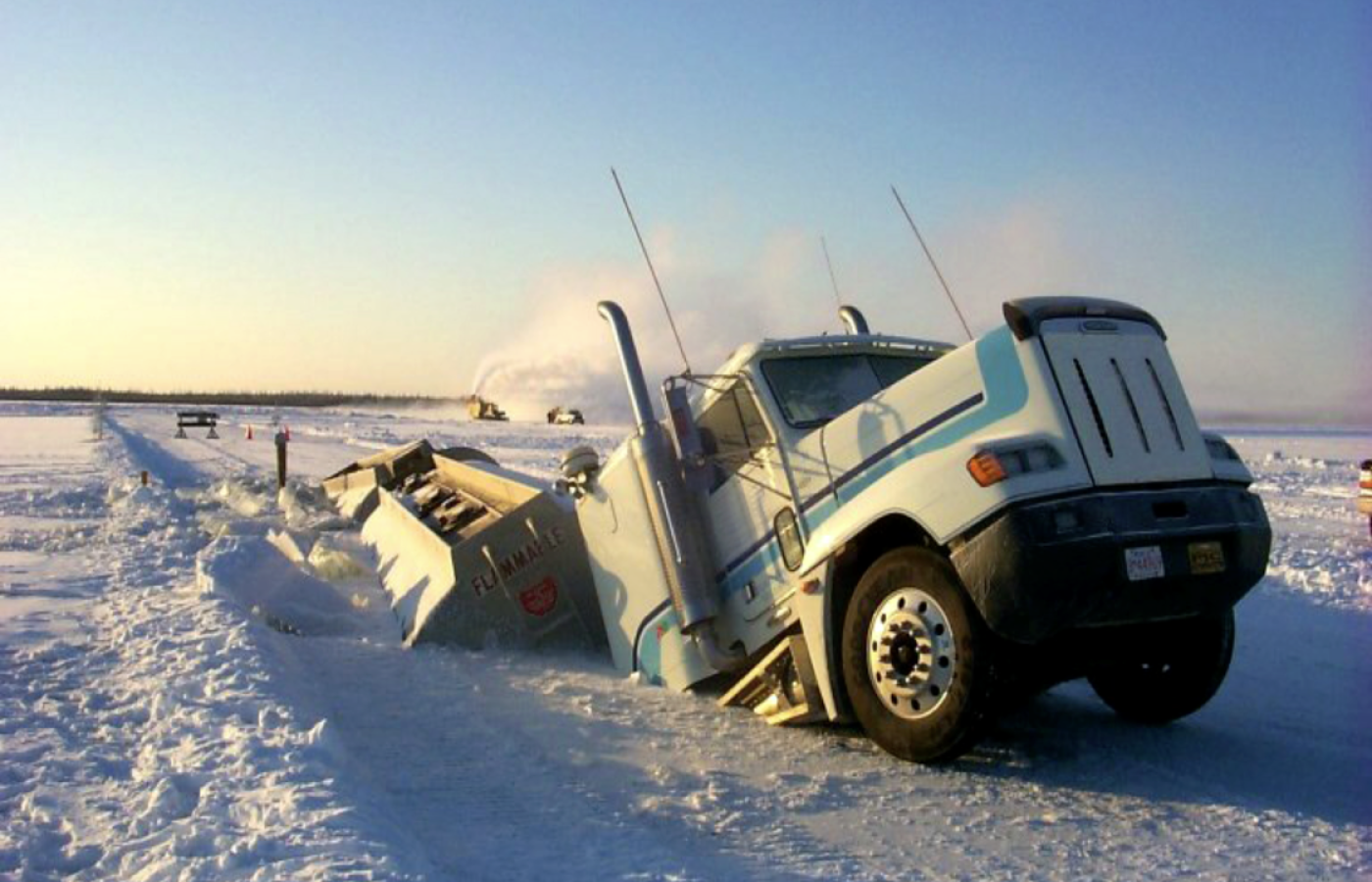 A truck broken through the ice road with only the cab protruding through the ice