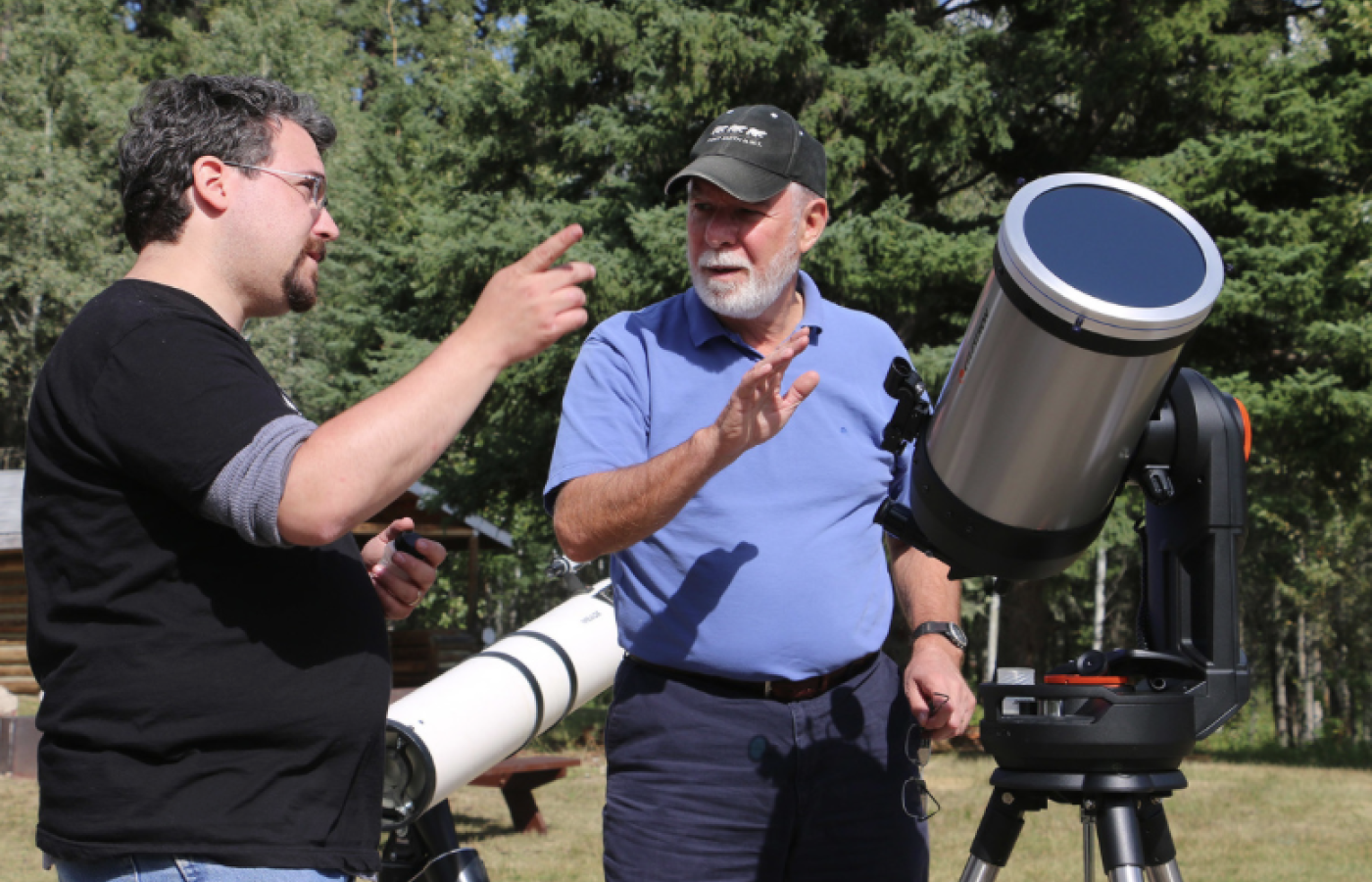 People standing and talking with a telescope beside them at the Dark Sky Festival in Fort Smith, NWT.