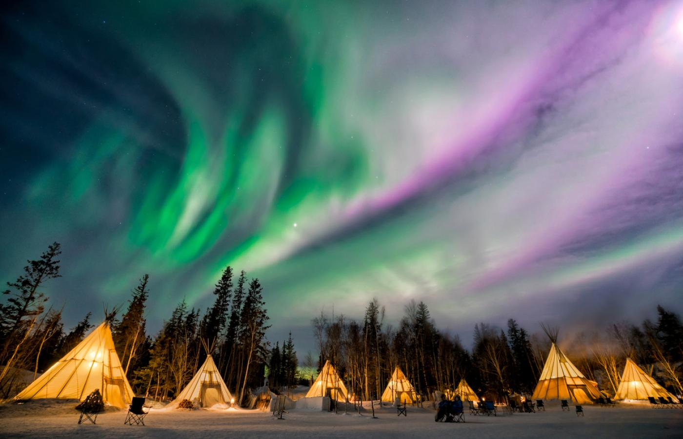 The Northern Lights above Aurora Village's teepee accommodations outside of Yellowknife, Northwest Territories, Canada