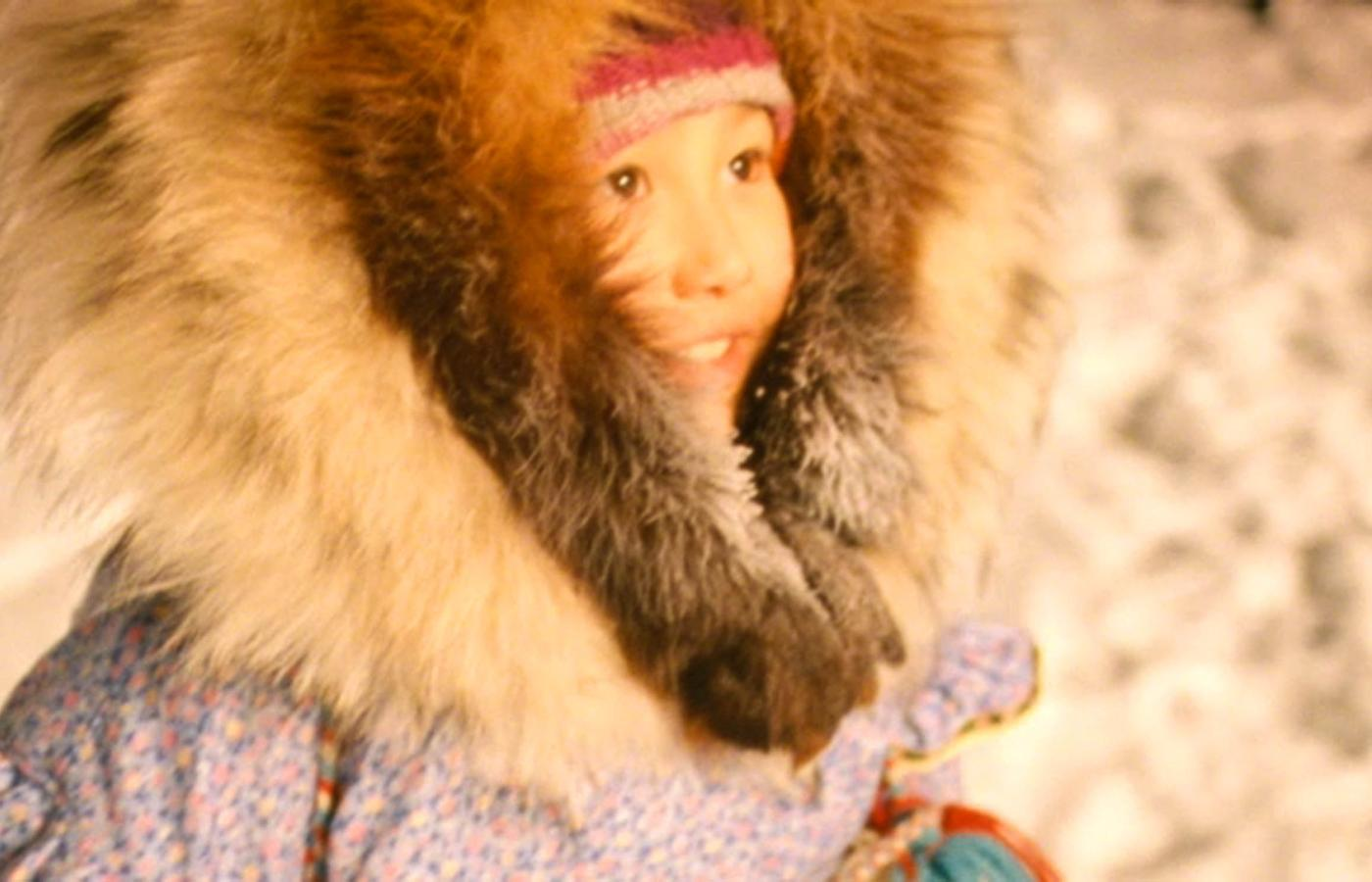 Young girl wearing a coat with fur trim on the hood at Inuvik's Sunrise Festival