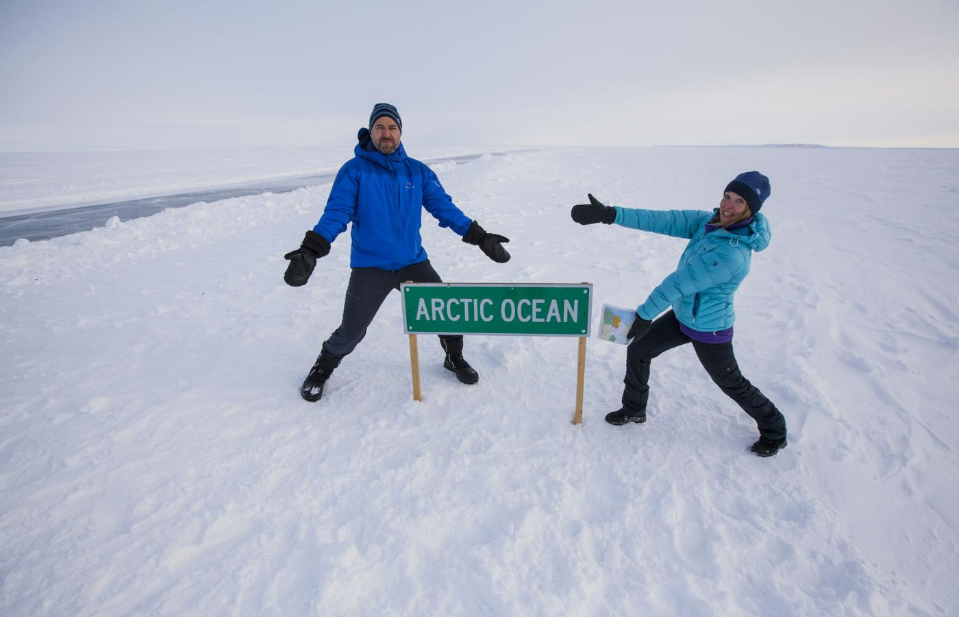 Two people standing at the frozen Arctic Ocean sign