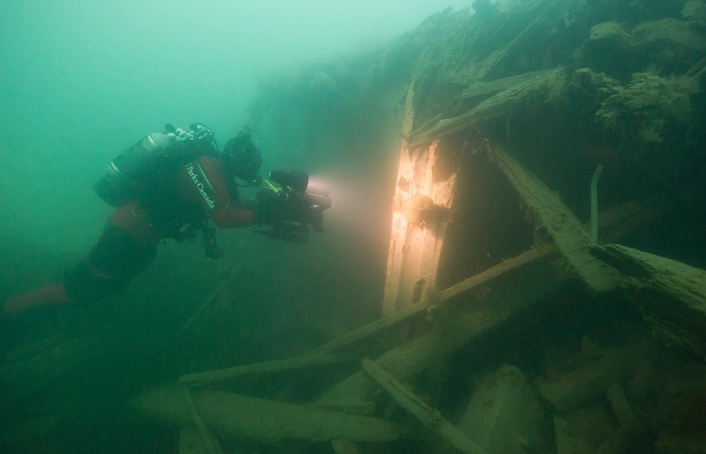 An underwater image of a Parks Canada diver examining the wreckage of a ship