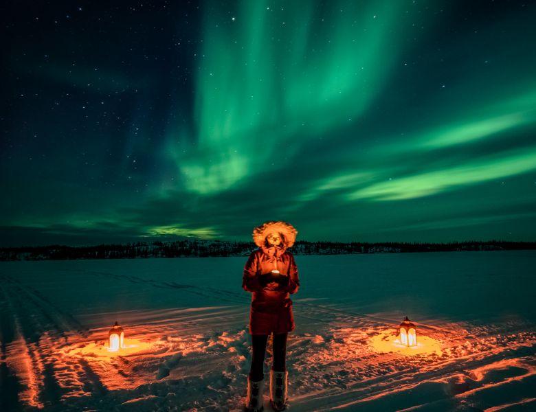 woman holding lantern in the snow under the aurora northern lights